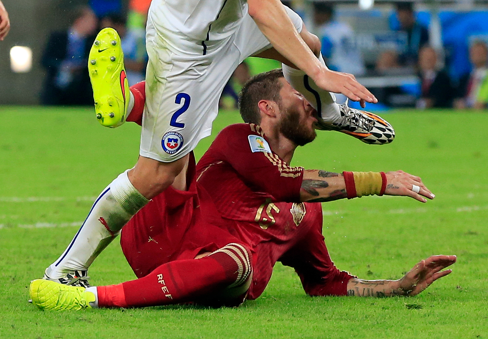 . Spain\'s Sergio Ramos takes the boot of Chile\'s Eugenio Mena in the face during the group B World Cup soccer match between Spain and Chile at the Maracana Stadium in Rio de Janeiro, Brazil, Wednesday, June 18, 2014.  (AP Photo/Bernat Armangue)