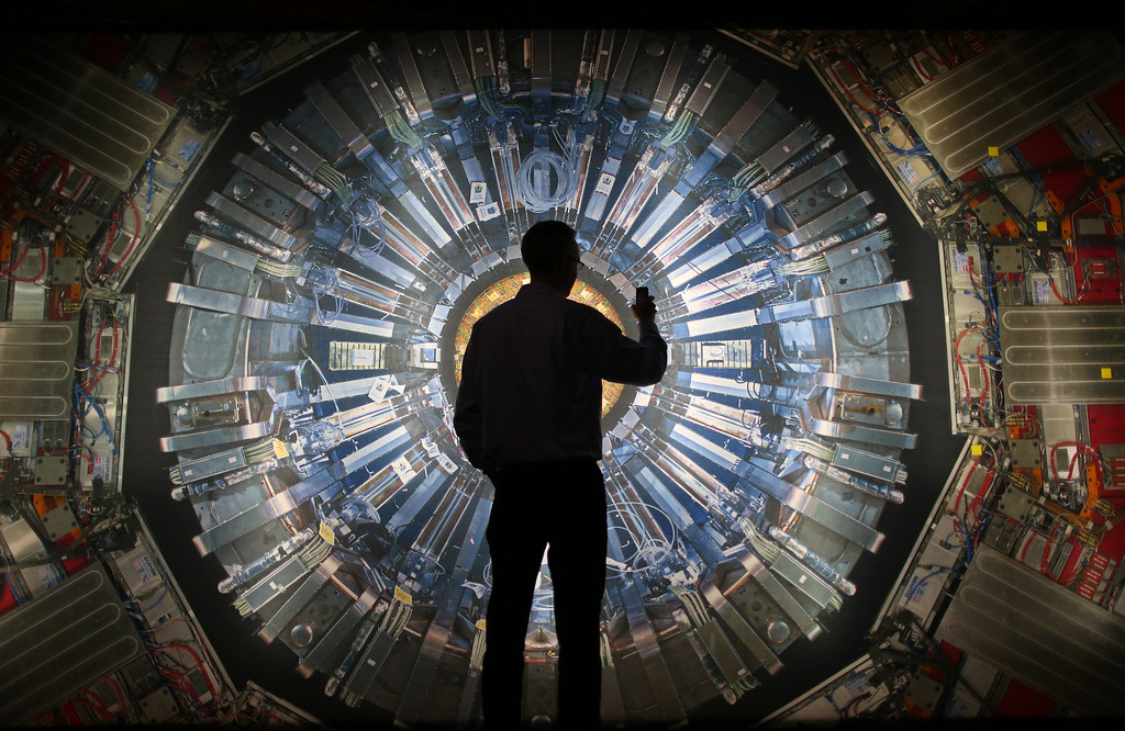 . A visitor takes a phone photograph of a large back lit image of the Large Hadron Collider (LHC) at the  Science Museum\'s \'Collider\' exhibition on November 12, 2013 in London, England.  (Photo by Peter Macdiarmid/Getty Images)