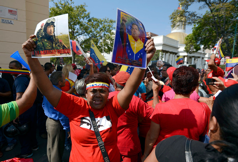 ". Supporters of Venezuelan President Hugo Chavez gather at Simon Bolivar Square in Caracas to celebrate after Chavez announced on Twitter that he had returned to the country from Cuba and is hospitalized at a military hospital in the Venezuelan capital, on February 18, 2013. Chavez returned to Venezuela early on Monday after spending more than two months in Cuba for cancer surgery and treatment, announcing his surprise homecoming via Twitter. ""We have arrived again to the Venezuelan motherland,\"" Chavez wrote. \""Thank you, God. Thank you, my beloved people. We will continue my treatment here.\""  JUAN BARRETO/AFP/Getty Images"