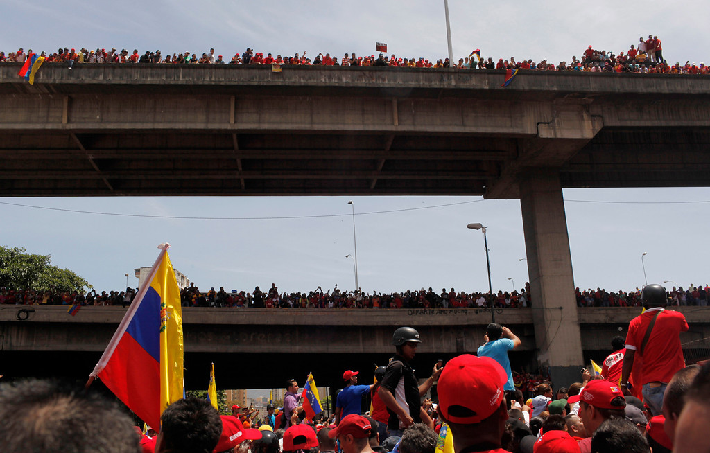 . Supporters stand on highway overpasses to get a view of the flag-draped coffin containing the body of Venezuela\'s late President Hugo Chavez being taken from the hospital, where he died on Tuesday, to a military academy in Caracas, Venezuela, Wednesday, March 6, 2013. (AP Photo/Rodrigo Abd)