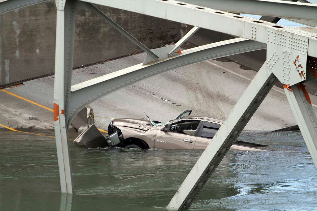 . A car is seen in the water as a span of highway bridge sits in the Skagit River May 24, 2013 after collapsing near the town of Mt Vernon, Washington late Thursday. The bridge collapse that sent cars and drivers tumbling into a frigid river in Washington state appears to have been caused when a semi-trailer truck carrying an oversize load struck a bridge support beam, officials said on Friday. The truck crossed the bridge safely before a portion of the structure collapsed, sending two vehicles and a mass of concrete and steel into the Skagit River Thursday evening. Three people had to be rescued, officials said.   REUTERS/Cliff DesPeaux