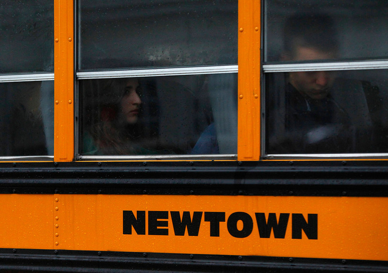 . Students ride a school bus in Newtown, Connecticut December 18, 2012.  The schools of Newtown, which stood empty in the wake of a shooting rampage that took 26 of their own at Sandy Hook Elementary, will again ring with the sounds of students and teachers on Tuesday as the bucolic Connecticut town struggles to return to normal. REUTERS/Eric Thayer