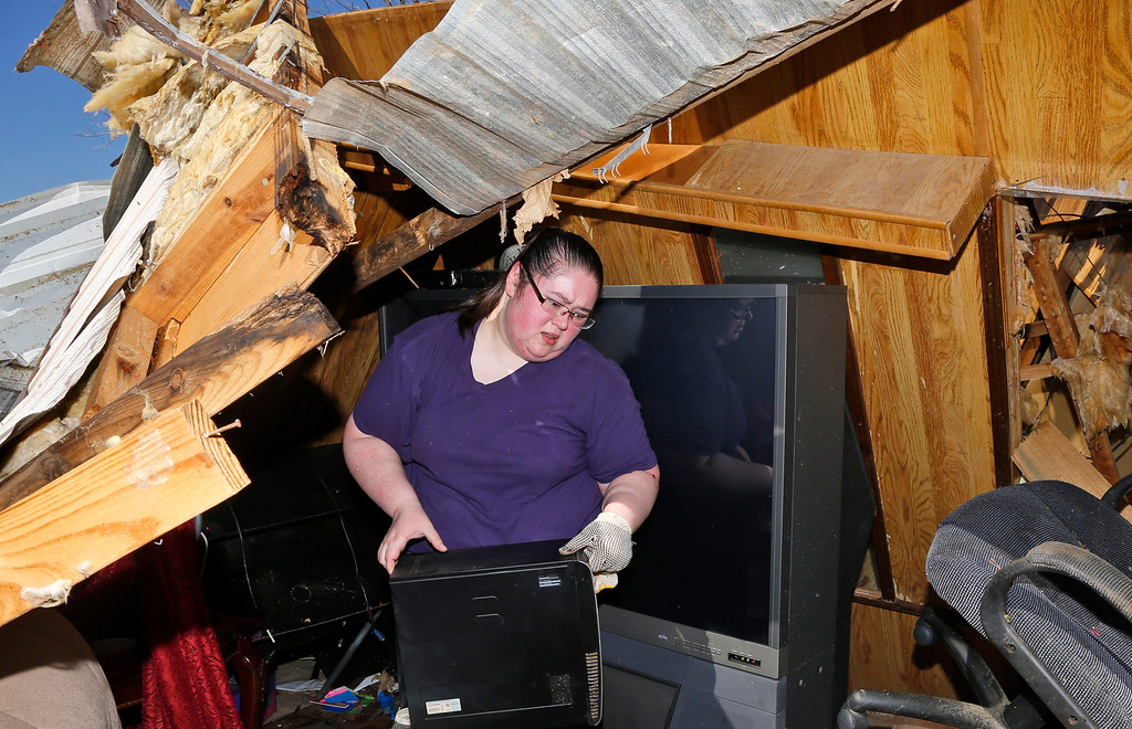 . Deidre Maxwell salvages items from her parent\'s tornado-damaged mobile home in Sand Springs, Okla., Thursday, March 26, 2015. (AP Photo/Sue Ogrocki)