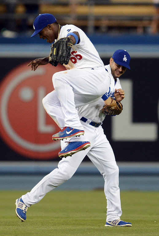 . The Dodgers\' Yasiel Puig #66 jumps on teammate Andre Ethier #16 after beating the Reds during their game at Dodger Stadium in Los Angeles Saturday, July 27, 2013. The Dodgers defeated the Reds 4-1. (Hans Gutknecht/Los Angeles Daily News)