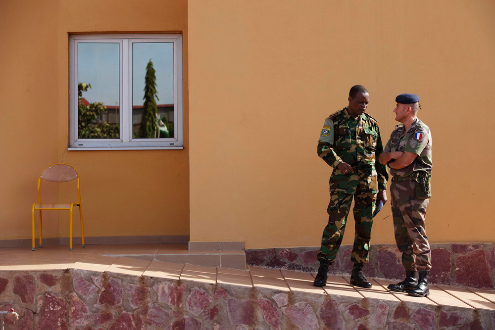 . A French army officer (R) talks to his Malian counterpart outside where a meeting is taking place for the intervention force provided by the ECOWAS grouping of West African states, in Bamako January 15, 2013. France kept up its air strikes against Islamist rebels in Mali as plans to deploy African troops gathered pace on Tuesday amid concerns that delays could endanger a wider mission to dislodge al Qaeda and its allies.    REUTERS/Joe Penney