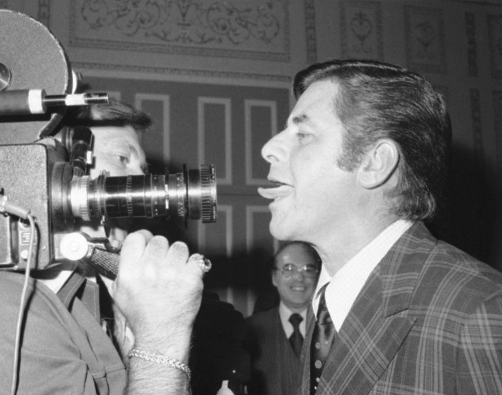 . Comedian Jerry Lewis, right, hams it up as he sticks out his tongue at a television camera during reception in his honor at a New York Hotel, Monday, June 7, 1976, New York.  (AP Photo/Ron Frehm)