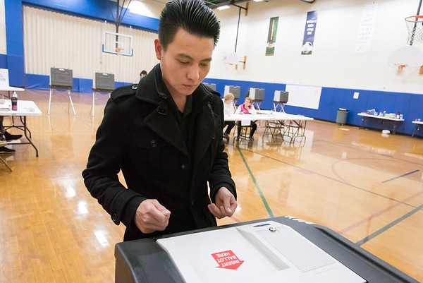 11/06/18 Wesley Bunnell | Staff Thanh Nguyen watches as his ballot is accepted into the tabulation machine at the Willard Elementary School voting location on Tuesday night.