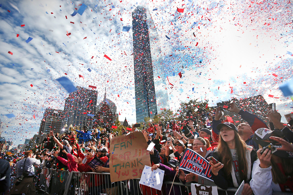 . Confetti showers fans in Copley Square as the Boston Red Sox baseball rolling rally passes by celebrating their World Series championship Saturday, Nov. 2, 2013, in Boston. (AP Photo/Elise Amendola)
