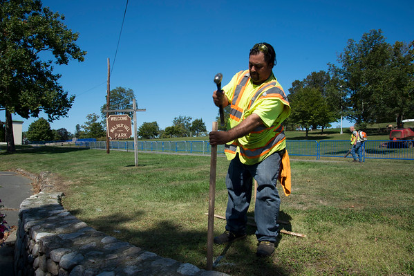 09/19/19 Wesley Bunnell | StaffrrCity workers were busy making improvements to Walnut Hill Park on Thursday as well as setting up security measures for the expected crowd for Sunday's visit by the Polish President. City employee Walter Rivera pounds sticks for temporary fencing going in at the park.