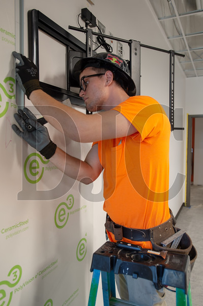 Andrey Kibukevich, an installer with Building Materials Specialities, installs an interactive white board. (Josh Kulla/DJC)