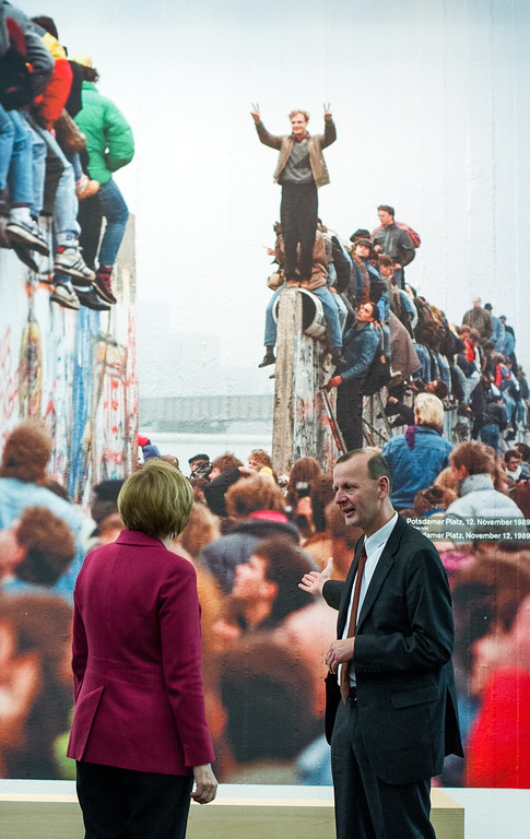 . German Chancellor Angela Merkel and Director of the Berlin Wall Foundation Axel Klausmeier visit the new permanent exhibition in the Berlin Wall memorial at Bernauer Strasse in Berlin, Germany, Sunday, Nov. 9, 2014. 25 years ago - on Nov. 9, 1989 - the East-German government lifted travel restrictions and thousands of East Berliners had pushed their way past perplexed border guards to celebrate freedom with their brethren in the West. (AP Photo/dpa, Bernd von Jutrczenka)