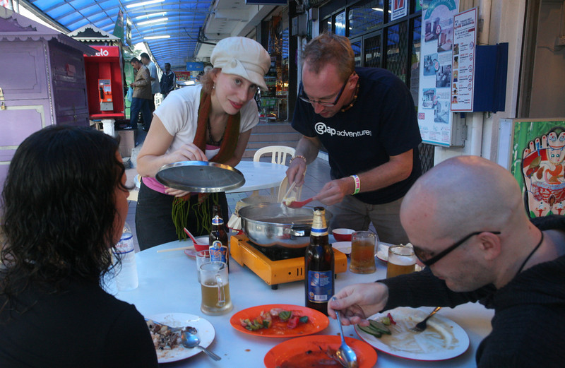 tourists cooking soup at a sidewalk cafe