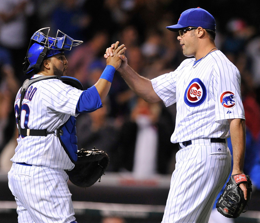 . Chicago Cubs closing pitcher Kevin Gregg, right, celebrates with catcher Dioner Navarro left, after defeating the Colorado Rockies 6-3 in a baseball game in Chicago, Wednesday, May 15, 2013. (AP Photo/Paul Beaty)