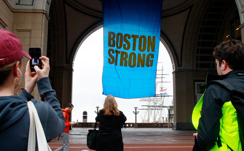 ". People photograph a banner reading ""Boston Strong\"" as it hangs at Rowes Wharf on the first anniversary of the Boston Marathon bombings, Tuesday, April 15, 2014, in Boston. (AP Photo/Bill Sikes)"