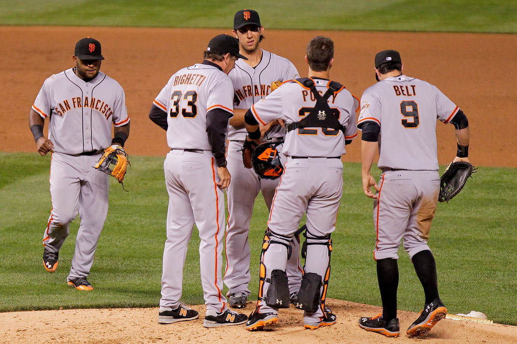 . San Francisco Giants starting pitcher Madison Bumgarner, third from left, is surrounded by teammates after giving up a bunt to Colorado Rockies starting pitcher Franklin Morales (56) during the fourth inning of a baseball game, Tuesday, April 22, 2014, in Denver. Giants first baseman Brandon Belt was given an error on the play. (AP Photo/Barry Gutierrez)