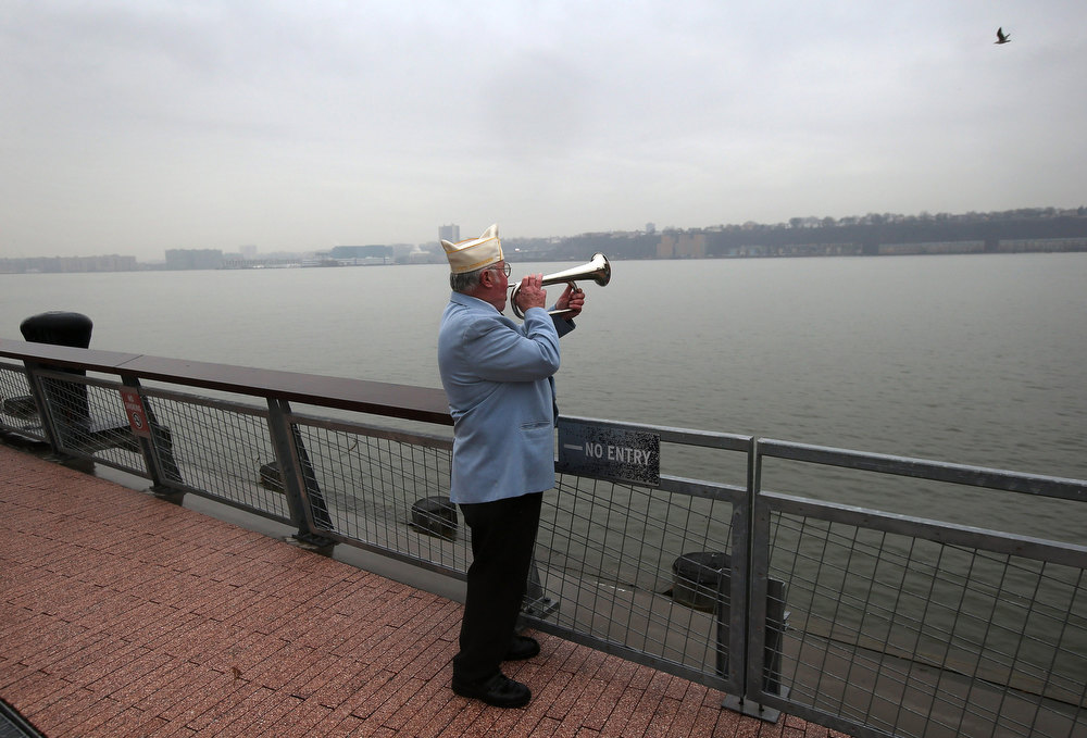 . Catholic War Veterans New York State Commander James Mullarkey plays Taps during a ceremony commemorating the 71st anniversary of the Japanese attacks on Pearl Harbor on December 7, 2012 in New York City. World War II survivors of Pearl Harbor from the New York metropolitan area participated in a wreath-laying ceremony next to the Intrepid Sea, Air and Space Museum, which was damaged in Hurricane Sandy and is undergoing repairs.  (Photo by John Moore/Getty Images)