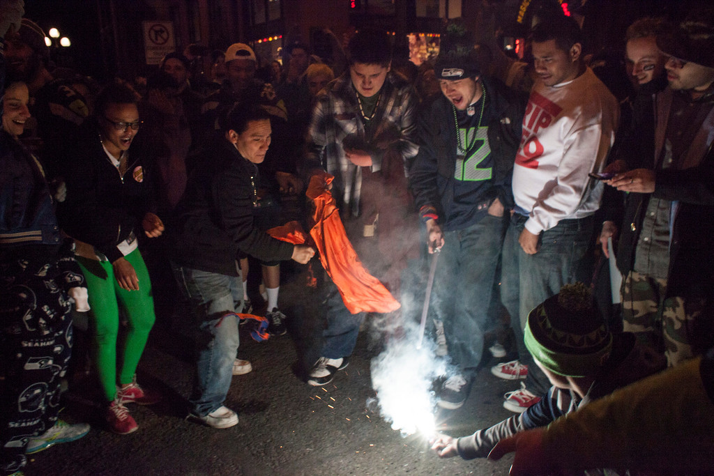 . Seattle Seahawks fans attempt to burn a Denver Broncos jersey while celebrating after watching the Seahawks win the Super Bowl on February 2, 2014 in Seattle, Washington. The Seahawks defeated the Broncos 43-8 in Super Bowl XLVIII.  (Photo by David Ryder/Getty Images)