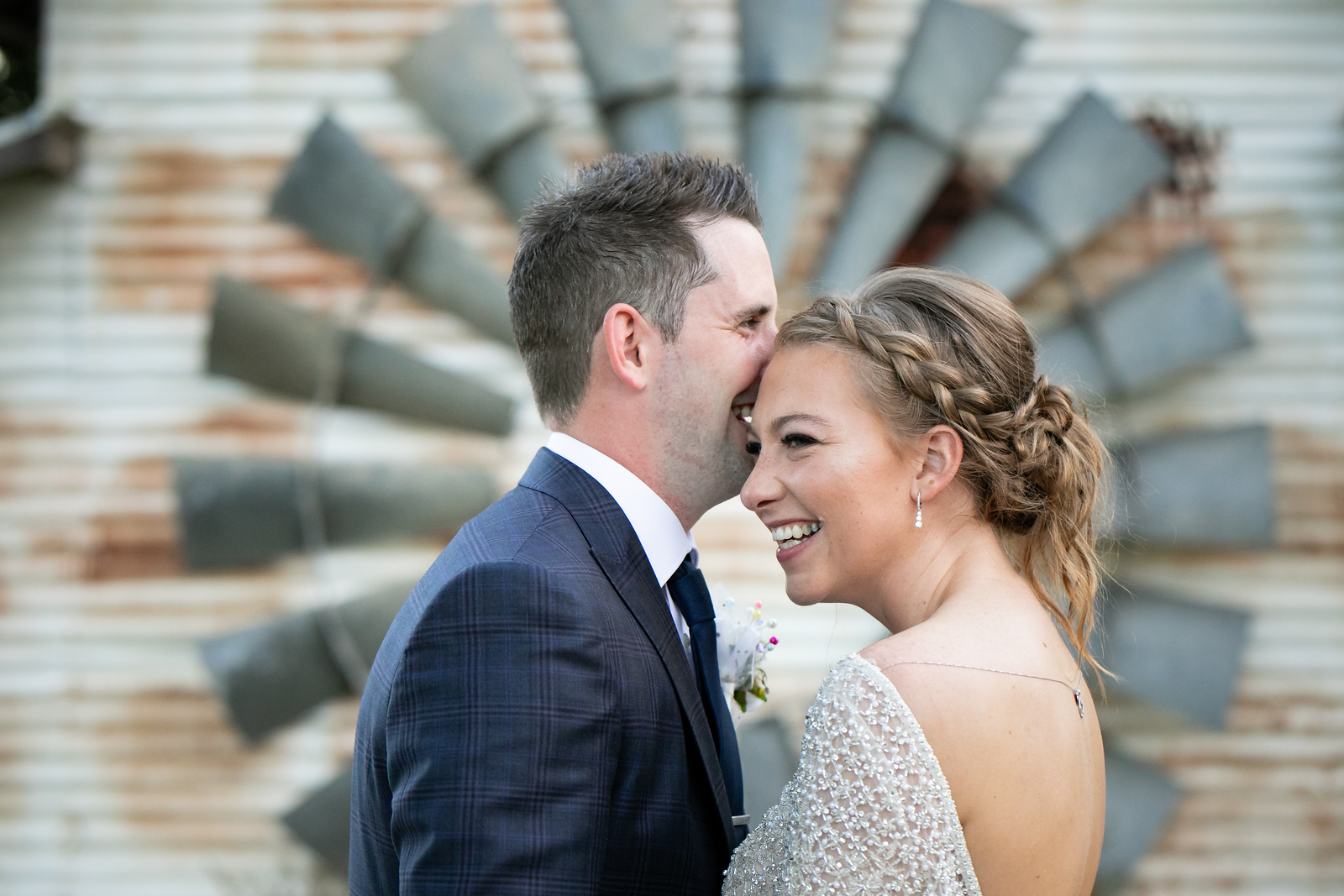 a bride and groom smiling as they hold each other in front of a rustic windmill