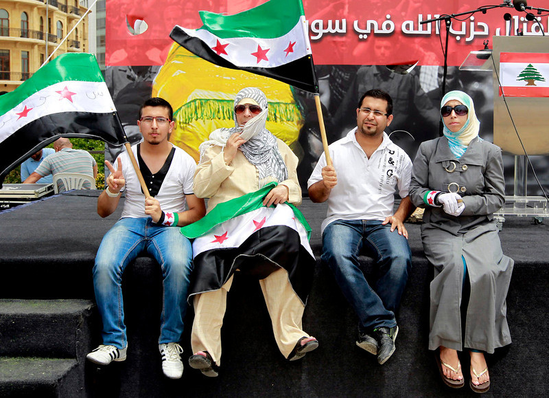 . A Syrian family hold Syrian revolution flags during a protest against the participation of Hezbollah\'s role in the Syrian war, at Martyrs square in Beirut, Lebanon, Sunday, June 9, 2013. A senior Lebanese military official says clashes have erupted outside the Iranian embassy in the capital between protesters opposing Hezbollah\'s participation in the Syrian war and unidentified locals, killing one demonstrator. (AP Photo/Bilal Hussein)