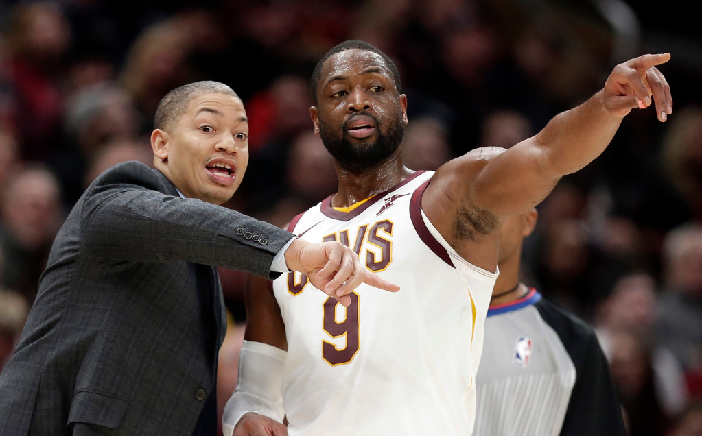 . Cleveland Cavaliers coach Tyronn Lue, left, talks with Dwyane Wade during the first half of an NBA basketball game against the Los Angeles Clippers, Friday, Nov. 17, 2017, in Cleveland. The Cavaliers won 118-113 in overtime. (AP Photo/Tony Dejak)