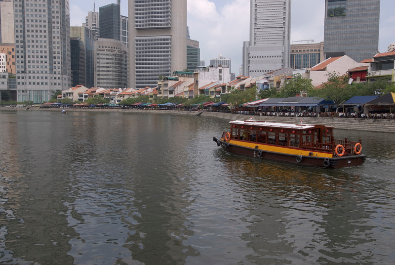 Boat cruising near the riverwalk in Downtown Singapore