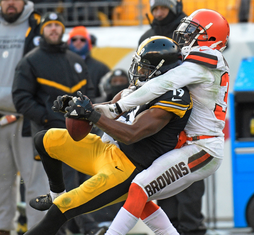 . Pittsburgh Steelers wide receiver JuJu Smith-Schuster (19) catches a pass with Cleveland Browns cornerback Jason McCourty (30) defending during the first half of an NFL football game in Pittsburgh, Sunday, Dec. 31, 2017. (AP Photo/Don Wright)