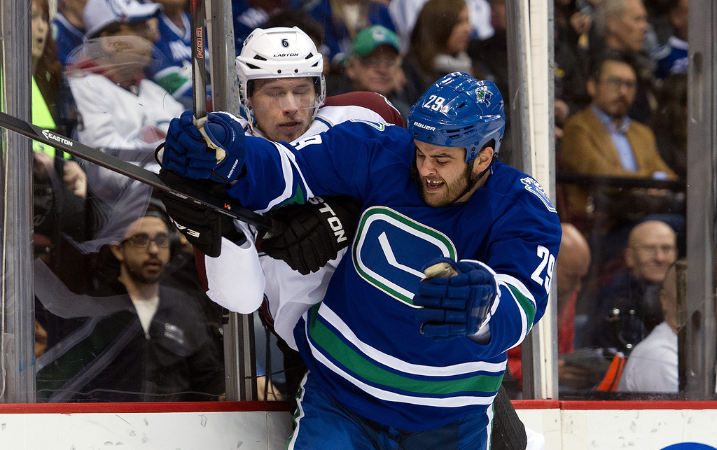 . Tom Sestito #29 of the Vancouver Canucks hits Erik Johnson #6 of the Colorado Avalanche along the end boards during the second period in NHL action on April 10, 2014 at Rogers Arena in Vancouver, British Columbia, Canada.  (Photo by Rich Lam/Getty Images)
