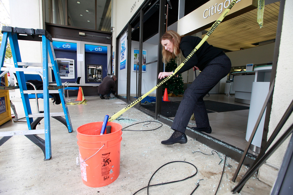 . Citibank branch manager at Dean Keenan, at the intersection of Shattuck and University avenues in Berkeley, Calif., steps through the hole where glass used to be to get a dust pan as she sweeps up broken glass on Monday, Dec. 8, 2014. (Laura A. Oda/Bay Area News Group)