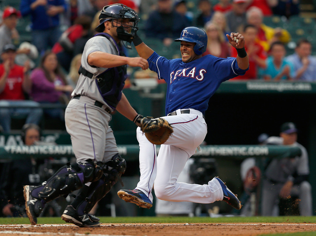 . ARLINGTON, TX - MAY 08:  Alex Rios #51 of the Texas Rangers slides into home plate against catcher Michael McKenry #8 of the Colorado Rockies to score in the bottom of the second inning at Globe Life Park in Arlington on May 8, 2014 in Arlington, Texas.  (Photo by Tom Pennington/Getty Images)