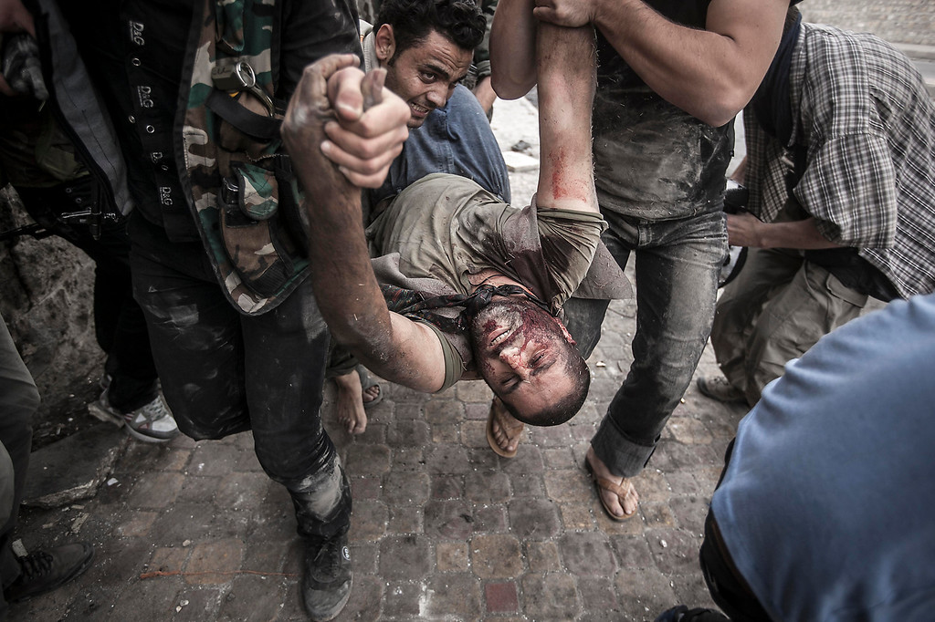 . In this Saturday, Oct. 20, 2012 photo, Free Syrian Army fighters carry a civilian away from the line-of-fire after he was shot twice, in his stomach and back, by a Syrian army sniper while walking near the frontline in the Bustan al-Qasr neighborhood of Aleppo, Syria. (AP Photo/Narciso Contreras)