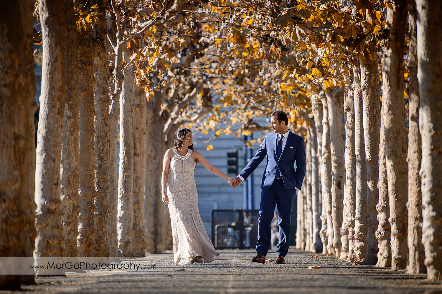 woman in beige dress and man in navy blue suit holding hands and walking between the trees in front of San Francisco City Hall