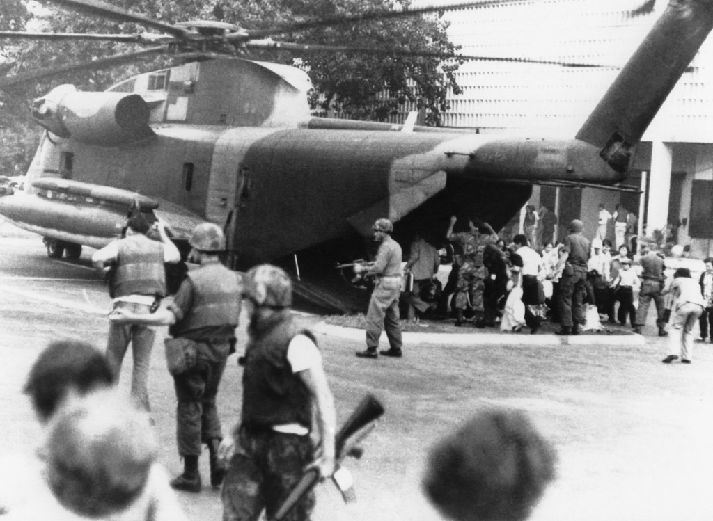 """. U.S. Marines disembark from a CH-53 \""""Jolly Green Giant\"""" to restore order and restrain crowds at the gates of the U.S. Embassy in Saigon during the final evacuation on April 29, 1975. (AP Photo/Frances Starner)"""