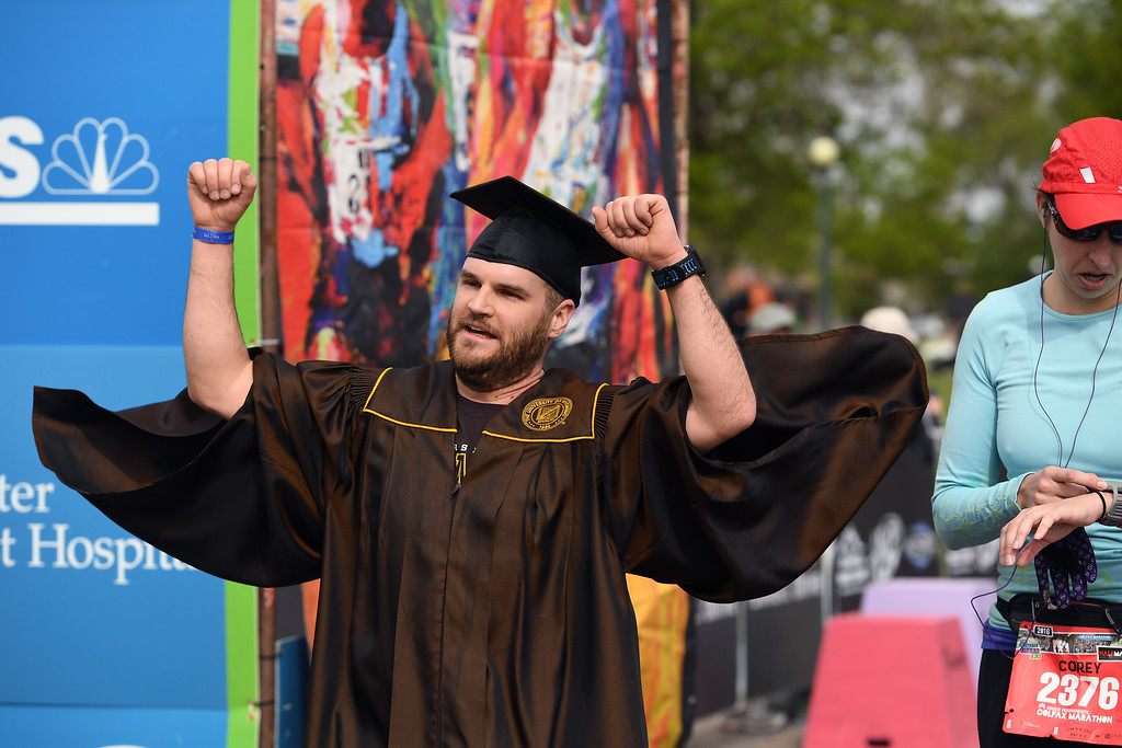 . DENVER, CO - MAY 15: Runner Chris Hennessy, who graduated just yesterday from University of Wyoming, pumps his fists in the air as he crosses the finish line of the  Colfax Half Marathon during the 11th annual Colfax Half Marathon on May 15, 2016 in Denver, Colorado.  Thousands of runners took part in the annual springtime race which included a marathon, a marathon relay,  a half marathon and the urban 10 miler.  (Photo by Helen H. Richardson/The Denver Post)