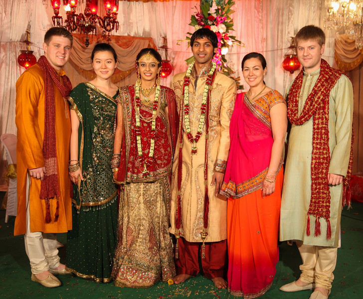 The whole group on stage in wedding attire.