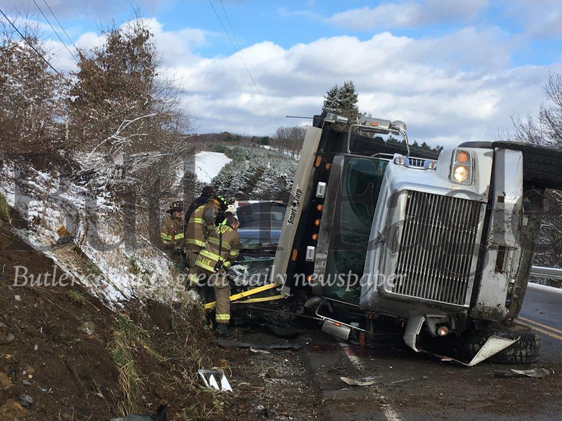 Unionville volunteer firefighters work to rescue a woman trapped inside her sport utility vehicle that collided with a dump truck about 10 a.m. Friday on Route 308 in Center Township. 3 Column Photo.