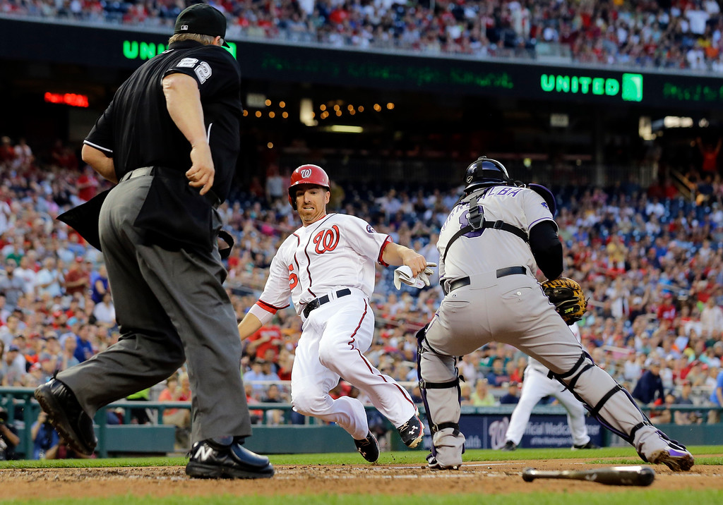 . Home plate umpire Joe West, left, watches as Washington Nationals\' Adam LaRoche, center, slides safely into home plate as Colorado Rockies catcher Yorvit Torrealba, right, attempts to tag him out during the fourth inning of a baseball game at Nationals Park, Thursday, June 20, 2013, in Washington. (AP Photo/Alex Brandon)