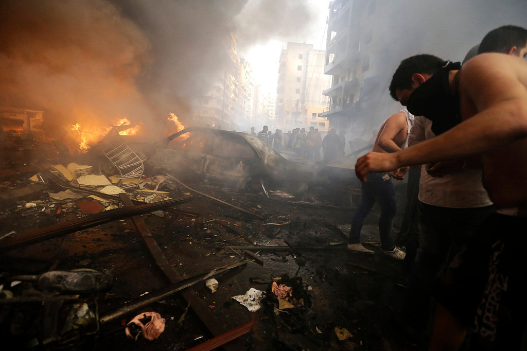 . Lebanese citizens and Hezbollah supporters gather next to burned cars and shops at the site of a car bomb explosion in southern Beirut, Lebanon, Thursday, Aug. 15, 2013. The powerful car bomb ripped through a southern Beirut neighborhood that is a stronghold of the militant group Hezbollah on Thursday, killing people and trapping others in burning buildings, the media said. (AP Photo/Hussein Malla)