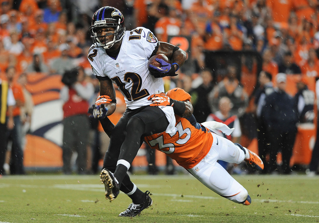 . Balltimore Ravens wide receiver Jacoby Jones is tackled by Duke Ihenacho of the Denver Broncos in the first quarter at Sports Authority Field at Mile High on September 5, 2013. (Photo by Steve Nehf/The Denver Post)