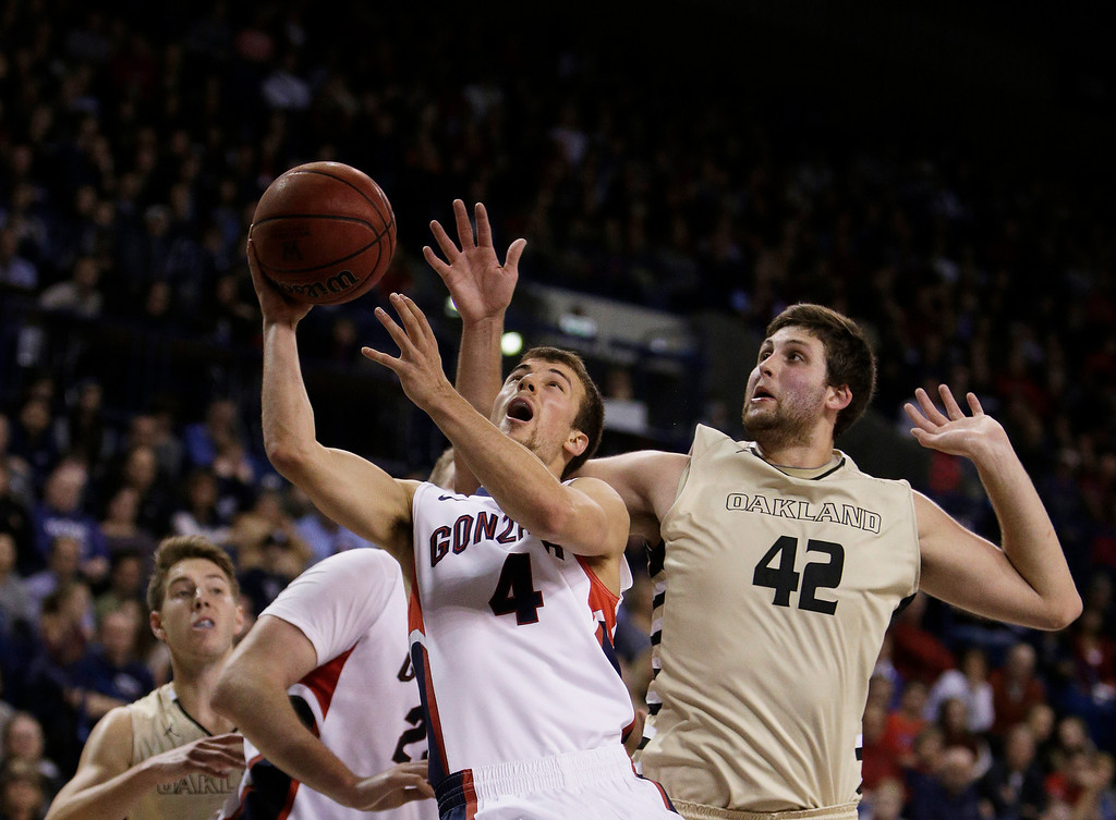 . Gonzaga�s Kevin Pangos (4) and Oakland\'s Corey Petros (42) fight for a rebound during the second half of an NCAA basketball game, in Spokane, Wash., on Sunday, Nov. 17, 2013. Gonzaga won 82-67. (AP Photo/Young Kwak)