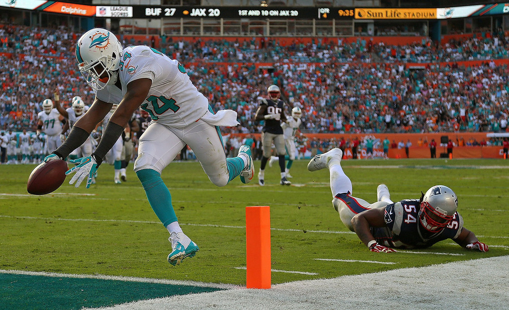 . Marcus Thigpen #34 of the Miami Dolphins scores a touchdown during a game against the New England Patriots at Sun Life Stadium on December 15, 2013 in Miami Gardens, Florida.  (Photo by Mike Ehrmann/Getty Images)