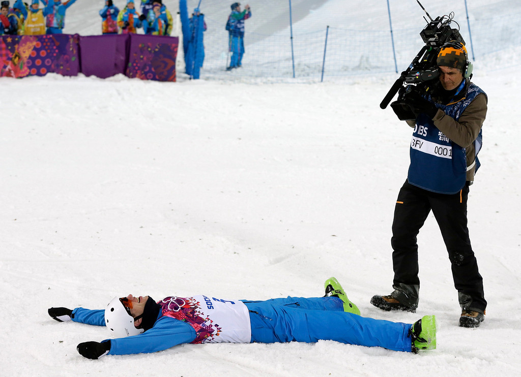 . A cameraman films Anton Kushnir of Belarus celebrating his gold medal in men\'s freestyle skiing aerials at the Rosa Khutor Extreme Park, at the 2014 Winter Olympics, Monday, Feb. 17, 2014, in Krasnaya Polyana, Russia. (AP Photo/Andy Wong)