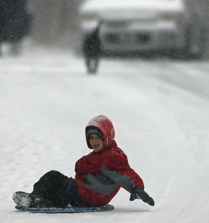 . Ryan Garner sleds down a street, Tuesday, Jan. 28, 2014, in Kennesaw, Ga. Georgians stocked up on ice-melting chemicals, school systems closed, and road crews prepared to clear snow and ice from highways as a winter storm took aim. (AP Photo/Mike Stewart)