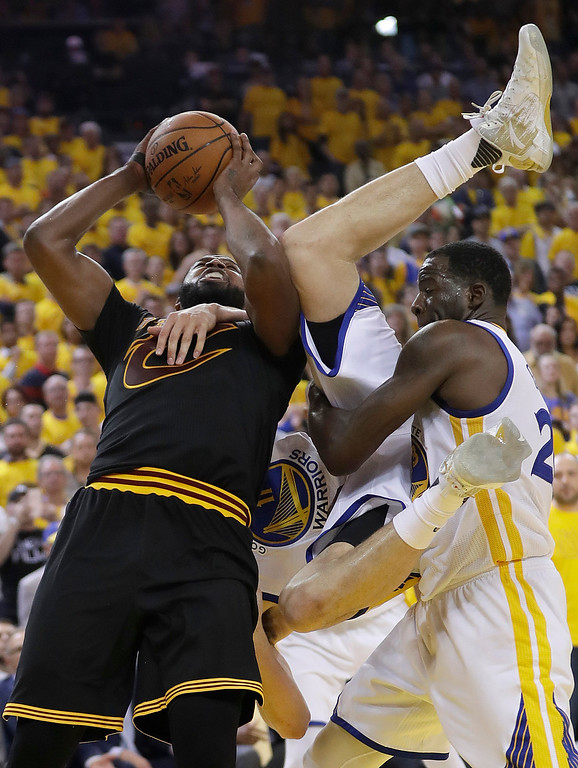. Cleveland Cavaliers center Tristan Thompson, left, shoots as Golden State Warriors guard Klay Thompson, center, is held by forward Draymond Green during the second half of Game 5 of basketball\'s NBA Finals in Oakland, Calif., Monday, June 12, 2017. (AP Photo/Marcio Jose Sanchez)