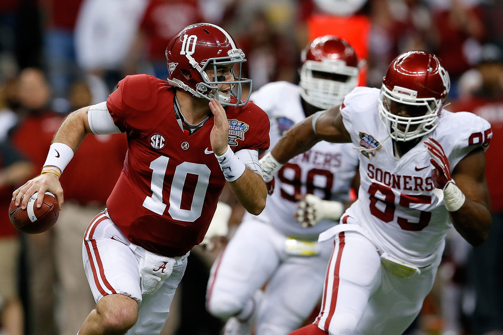 . NEW ORLEANS, LA - JANUARY 02:  AJ McCarron #10 of the Alabama Crimson Tide runs with the ball past Geneo Grissom #85 of the Oklahoma Sooners during the Allstate Sugar Bowl at the Mercedes-Benz Superdome on January 2, 2014 in New Orleans, Louisiana.  (Photo by Kevin C. Cox/Getty Images)