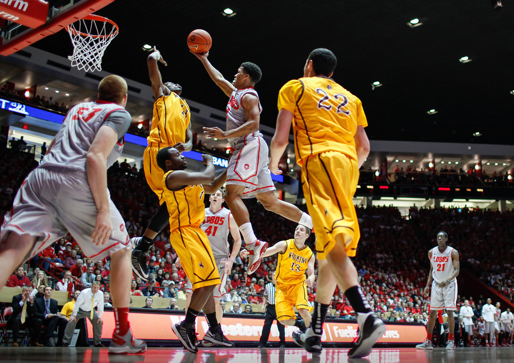 . New Mexico\'s Cleveland Thomas tries to shoot over Wyoming\'s Derek Cooke Jr., who blocked the shot during the first half of an NCAA college basketball game in Albuquerque, N.M., Saturday, March 2, 2013. (AP Photo/ Craig Fritz)