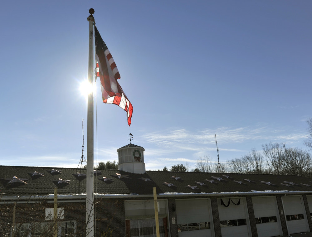 Description of . A flag outside the  Sandy Hook Fire department in Newtown, Connecticut on January 3, 2013.  Students at the elementary school where a gunman massacred 26 children and teachers last month were returning Thursday to classes at an alternative campus described by police as