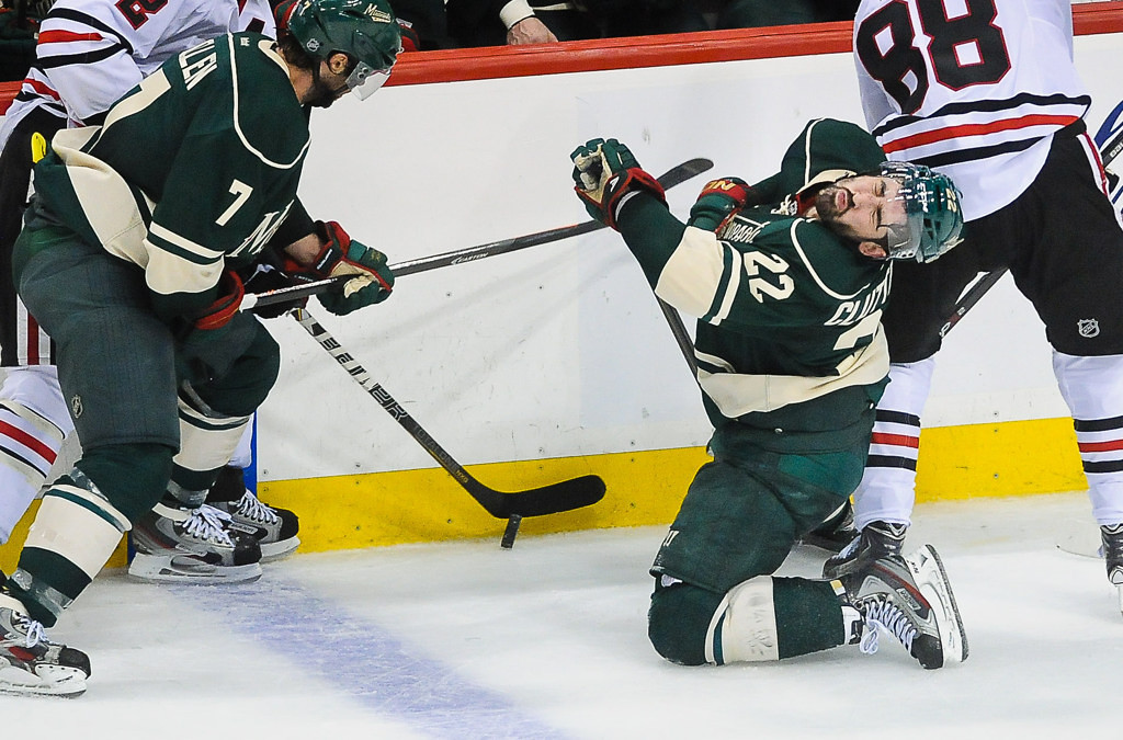 . Minnesota right wing Cal Clutterbuck is slapped in the face with a stick in the third period against the Blackhawks.  (Pioneer Press: Ben Garvin)