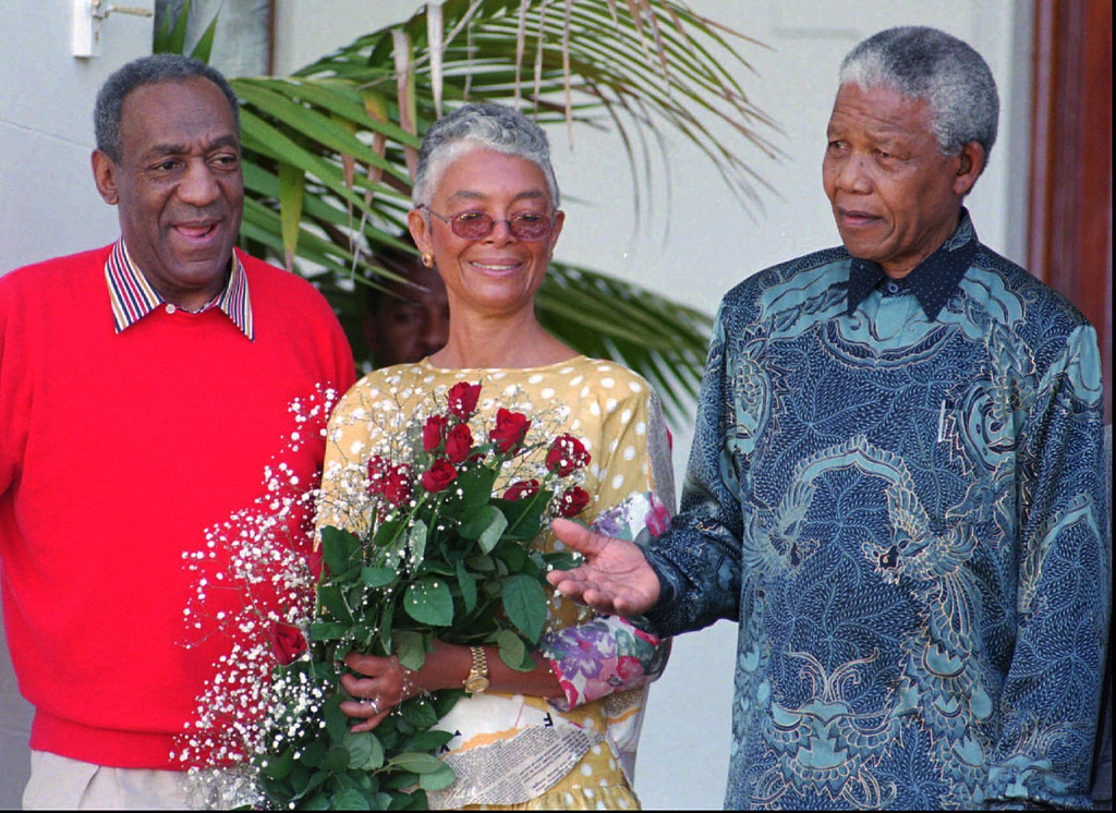 . Camille Cosby holds a bunch of flowers presented to her on the ocassion of her birthday flanked by her husband American entertainer Bill Cosby, left, and President Nelson Mandela Thursday, March 20, 1997 in Cape Town. Cosby will perform on Robben Island later for visiting U. S. first lady Hillary Rodham Clinton, Mandela and United Nations Secretary-General Kofi Annan at a charity performance. (AP Photo/Sasa Kralj)