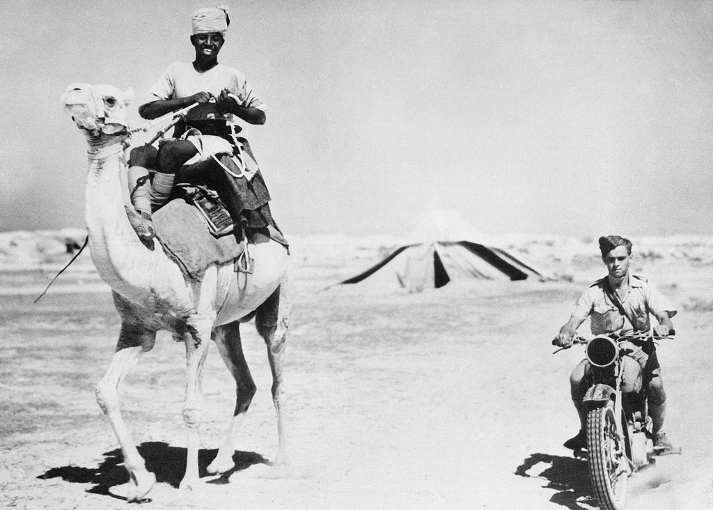 . The racing camel of the Sudanese and the motorcycle of the R.A.F. rider present a contrast in civilizations in the battle zone of the Western Desert in North Africa, Jan. 20, 1941. (AP Photo)
