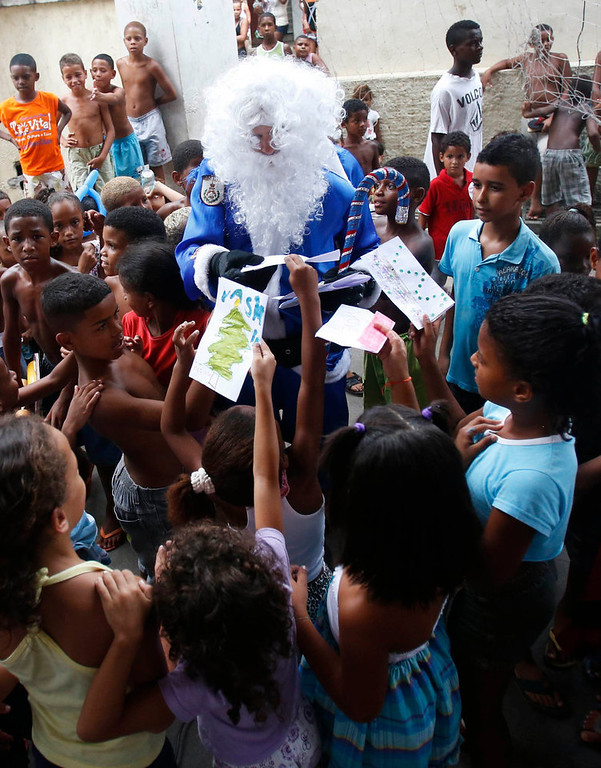 . A policeman of the Peacekeeping Police Unit (UPP) dressed up as Santa Claus in Rio de Janeiro\'s military police colours, plays with children during a Christmas party at Macacos slum in Rio de Janeiro December 20, 2012. REUTERS/Ricardo Moraes
